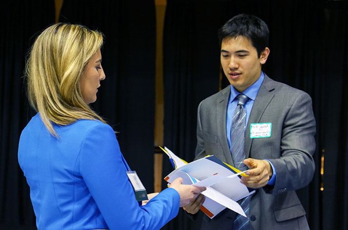 Student at the career fair talking to an employer