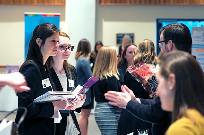 Students at a career fair talking with employers