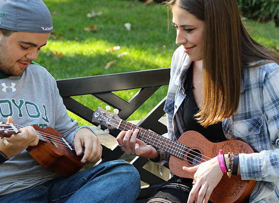 Two students playing ukuleles while sitting on a bench outside
