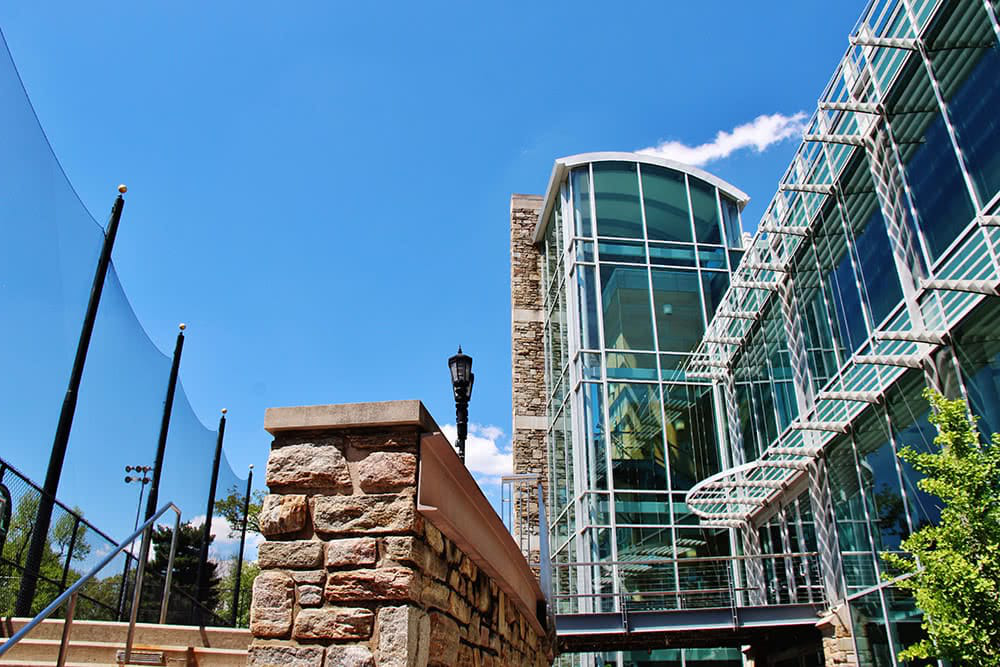The tall glass windows of the student center in front of a blue sky
