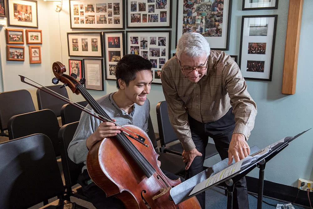 A profess要么 points at music while a student sits nearby with a cello
