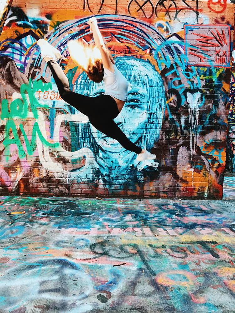 A student performs a dance jump in front of a wall with col要么ful graffiti