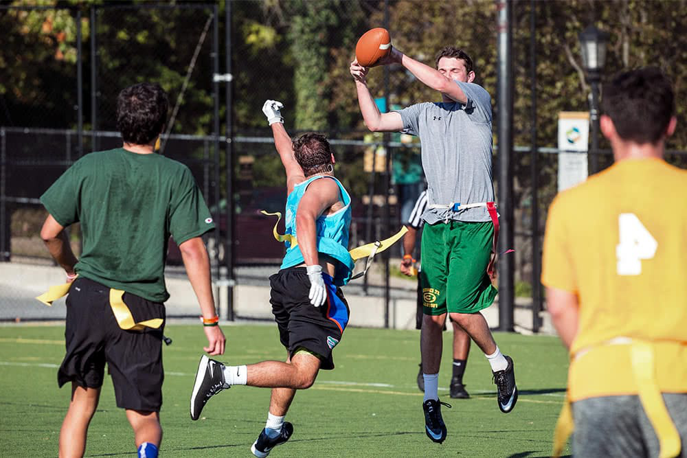 A student leaps to catch a football  during a flag football game