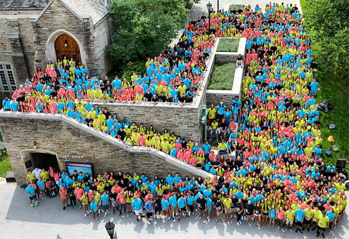 A birds-eye view of the class of 2023 wearing blue, yellow, black, and pink shirts