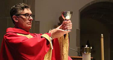 President Linnane wearing red robes and holding a goblet