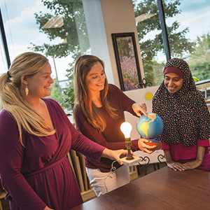 Loyola graduate education students learning how to teach about the earth and sun using a globe and lightbulb in one of their graduate school courses.