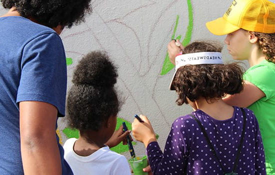 Young children helping to paint a mural along York Road