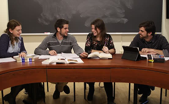 Four students having a discussion around a classroom table