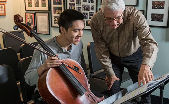 A student holding a cello and a professor looking at sheet music